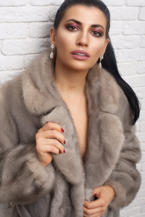 Crop young alluring woman with makeup in pearl earrings and fur coat looking at camera in daytime