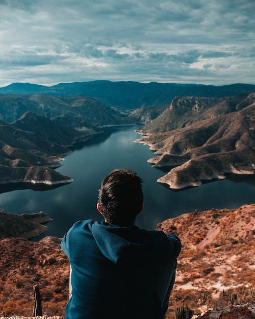 Man in Blue Hoodie Sitting on Brown Rock Formation Looking at Lake