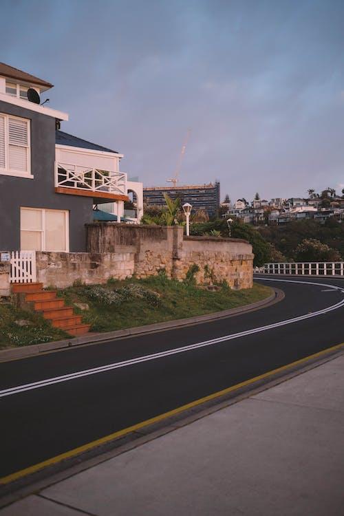 Asphalt road in residential district in town at sundown
