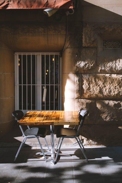 Cafe terrace with small wooden table and chairs placed near aged stone building on sunny day