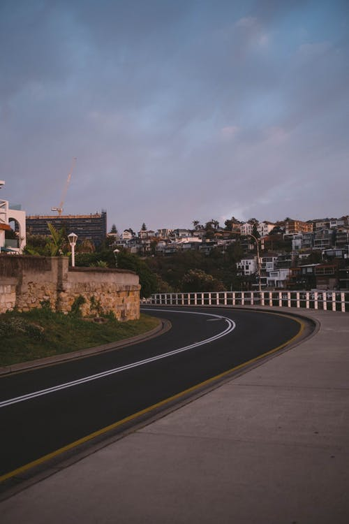 Curvy road in mountainous town under cloudy sky at sunset