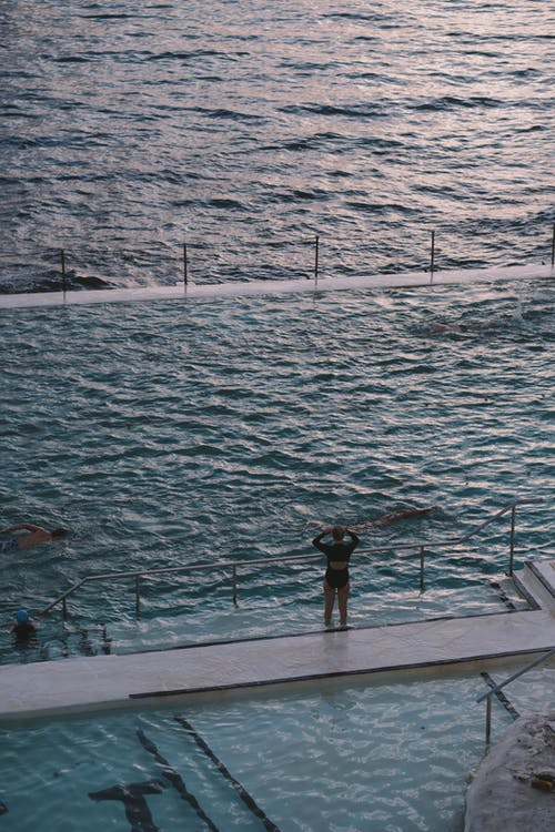 From above of unrecognizable tourists swimming in outdoor pool near rippling sea during summer holidays
