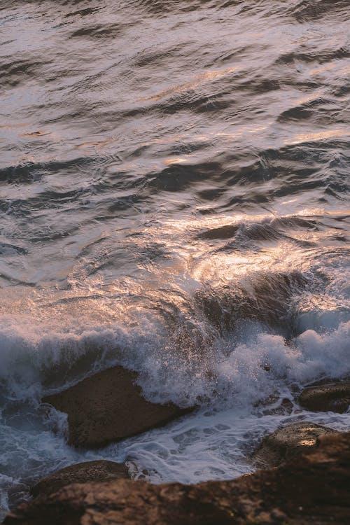Foamy sea washing rocky beach at sundown