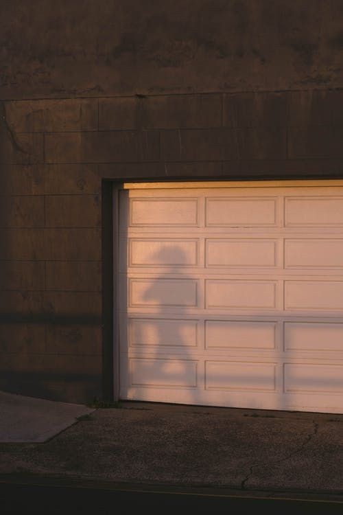 Shadow of unrecognizable person running on city street near stone building with white gates at sunset