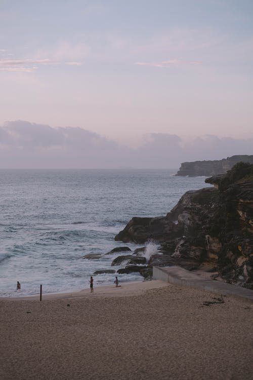 Scenic landscape of waving ocean splashing on empty sandy beach and rocky cliff against cloudy sunset sky