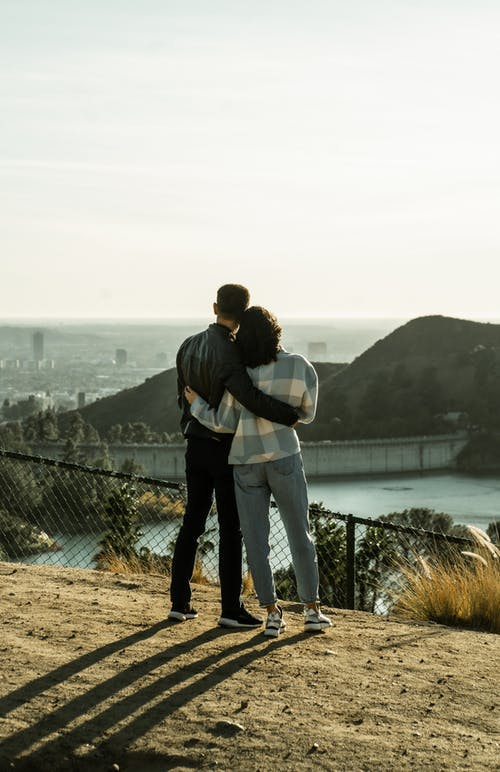 Back view of full length unrecognizable couple in casual clothes standing on bank of reservoir hugging and admiring view