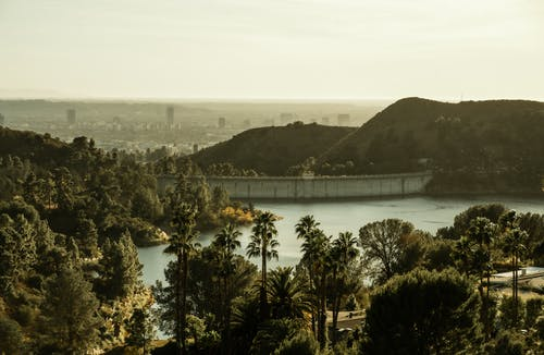 Amazing scenery of Hollywood Reservoir and dam amidst green verdant trees and hills in California on sunny day