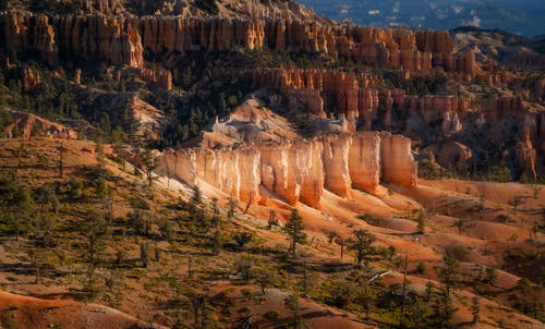 Picturesque scenery of rough sandstone formation with stiff slopes amidst sandy terrain and random vegetation