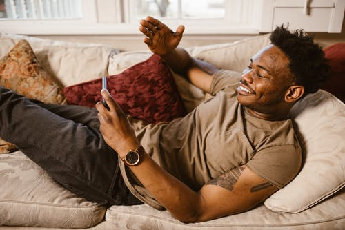 Man Lying on the Couch while Using his Smartphone