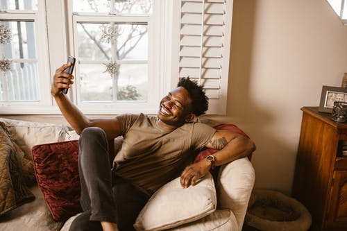 Happy Man Sitting on Couch while Having a Video Call