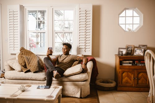 Man Sitting on Couch while Using Cellphone