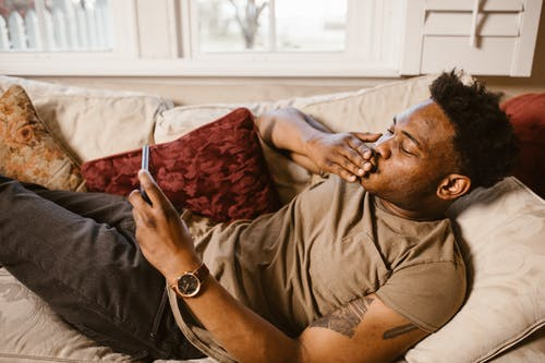 Man Lying Down on Couch while Having a Video Call