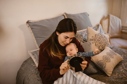 Mother Holding Her Baby while Looking at a Picture Frame