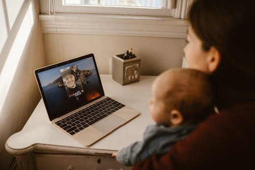 Woman Holding Her Baby while Having a Video Call Using a Laptop