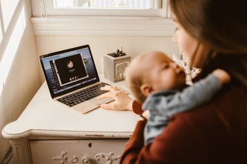 Mother Carrying her Baby while Calling Her Husband on Laptop