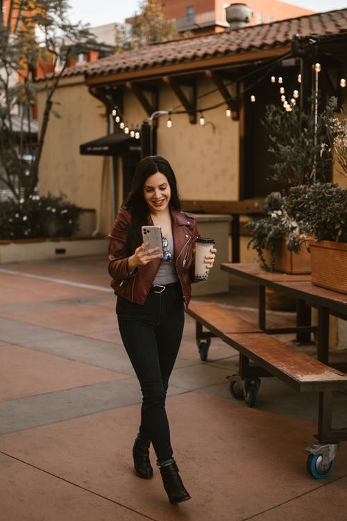 Woman in Black Pants and Brown Leather Jacket Holding Pink Leather Sling Bag