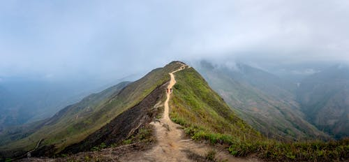 Travelers walking along path in hazy mountainous terrain