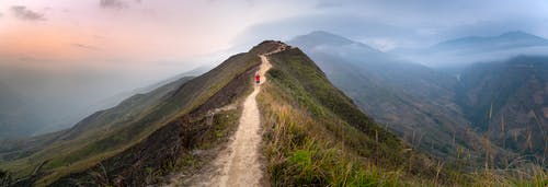 Wide angle of travelers walking on narrow path of hill covered with grass located against mountain range in haze