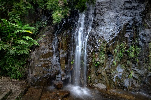 Waterfall stream flowing from rocky cliff
