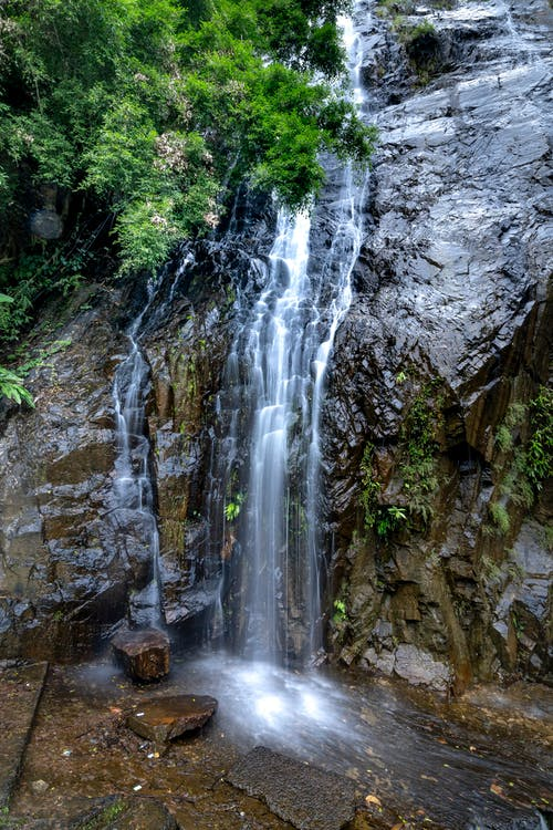 Waterfall falling from wet rocky cliff
