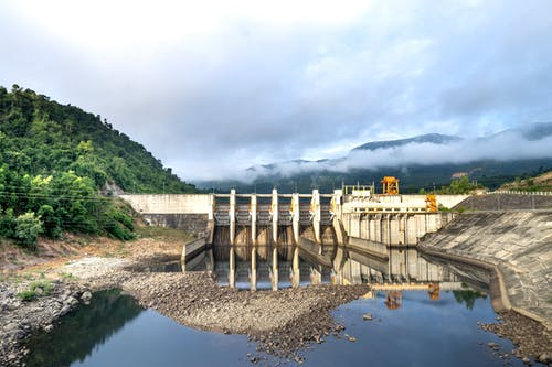 Industrial hydroelectric power plant located near river and stony coast against green mountain range covered with mist on summer day