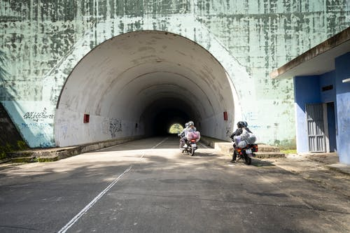Anonymous people riding motorbikes near tunnel
