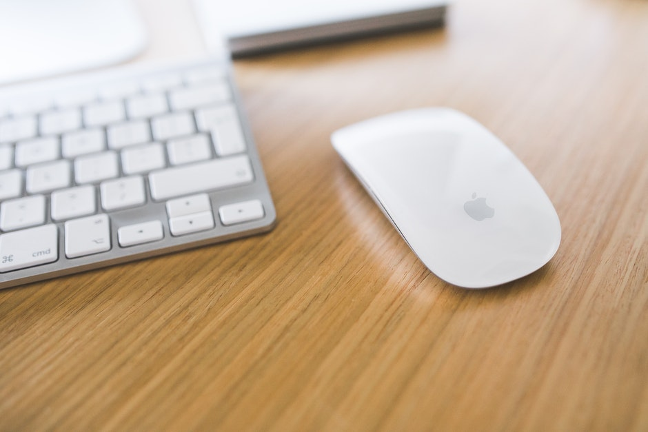 White Apple mouse and keyboard on a wooden desk