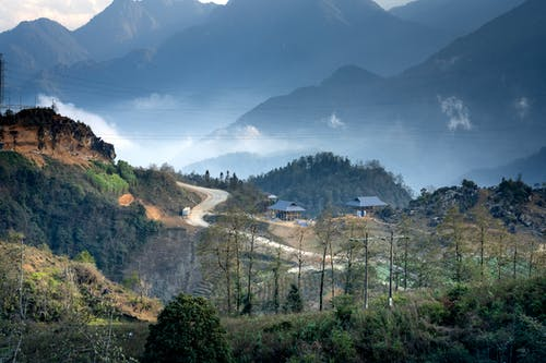 Scenic view of small settlement and curvy road going through lush valley in mountainous valley