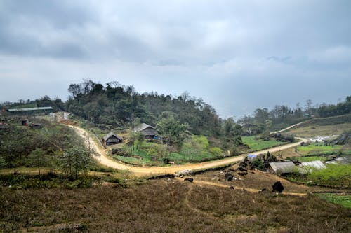Scenery of narrow curvy roadway going through verdant hilly area between rural houses on cloudy summer day
