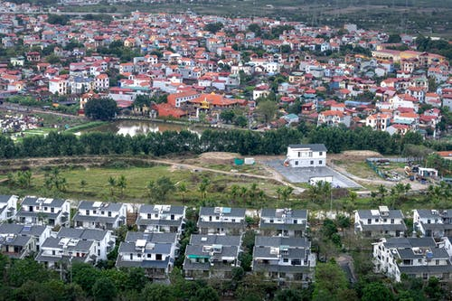 Drone view modern residential cottages located on grassy suburb district of modern town on summer day