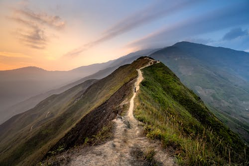 Scenery of narrow footpath on lush hilltop in picturesque highlands