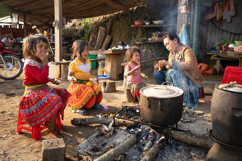 Asian mother and girls sitting near campfire in indigenous village