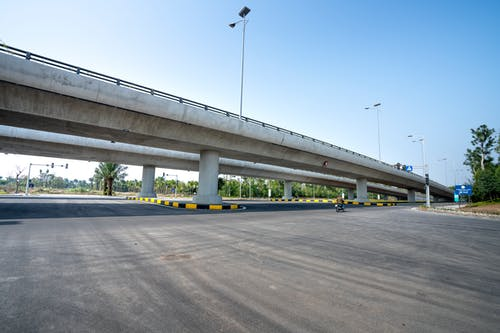 Unrecognizable motorcyclist on road against bridge in city