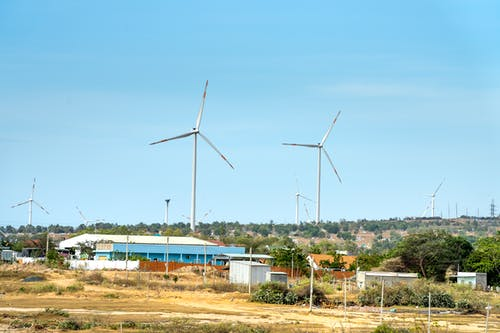 Scenic view of wind turbines against houses under cloudy blue sky in countryside in daytime