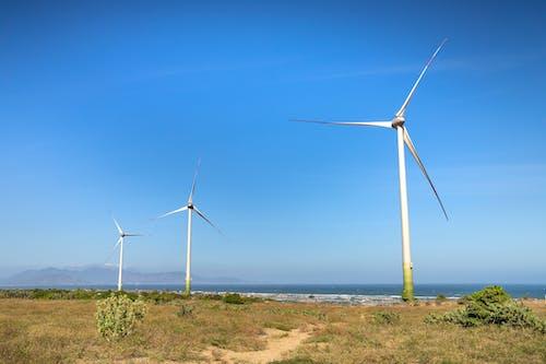 Windmills on land against sea and ridge under blue sky