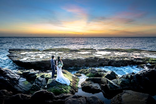 Back view of unrecognizable young bride and groom inelegant outfits standing on rough rocky boulder and admiring sunset over ocean