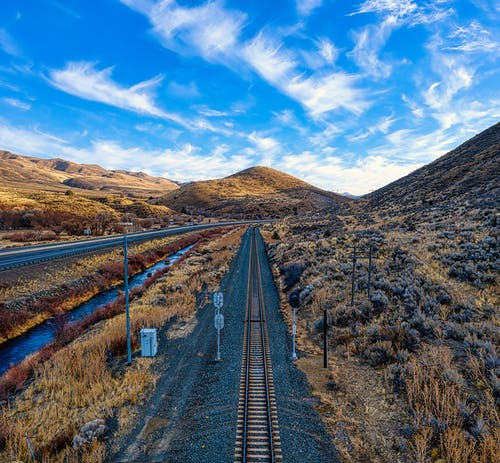 Empty straight railway tracks going through hilly area covered with grass against blue cloudy sky in rural terrain in countryside