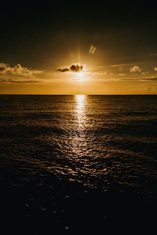 Wavy sea under cloudy sky with shiny sun at dusk