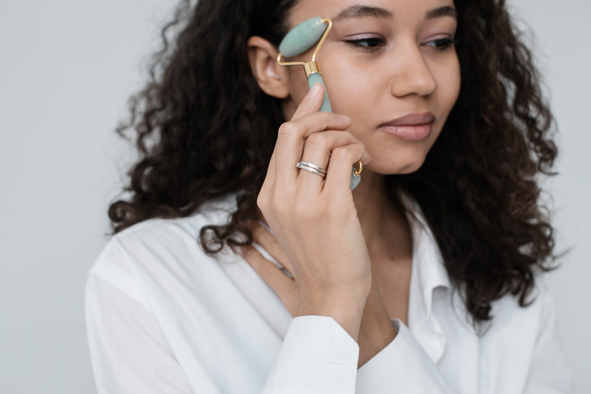 a woman rolling a jade roller on her face