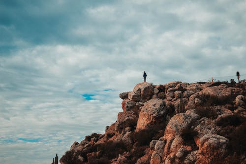 Person Standing on Brown Rock Formation Under White Clouds