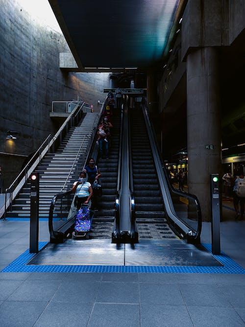 Anonymous passengers standing on moving escalator in underground metro station