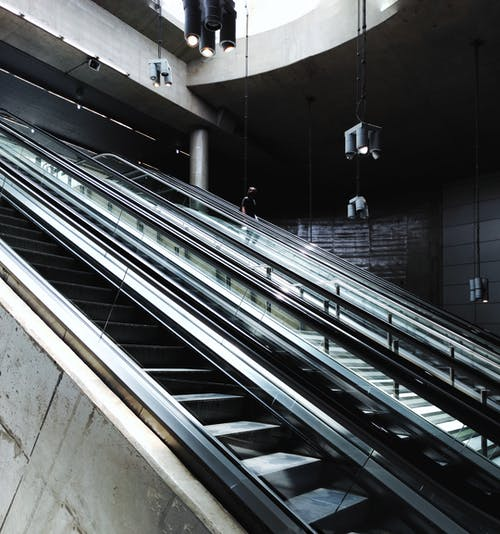 Unrecognizable passenger going down on moving staircase inside of underground railway station in daylight