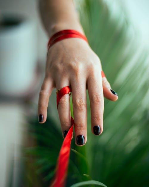 Person Wearing Silver Ring With Red Manicure