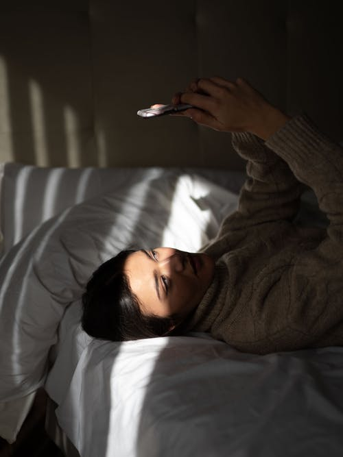 Relaxed young lady lying on bed and using smartphone