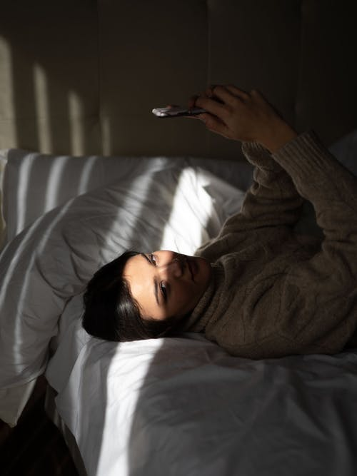 Side view of confident young female in warm sweater recreating on soft bed with smartphone in hands and looking at camera