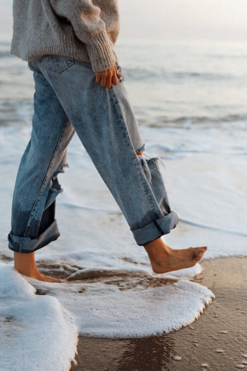 Side view of crop unrecognizable barefooted female tourist in stylish jeans and sweater walking on sandy beach washing by foamy waves of ocean during holidays