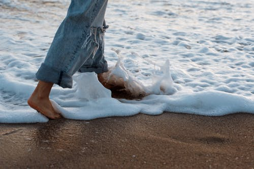Side view of crop faceless barefooted female traveler splashing foamy waves with feet while walking on ocean sandy beach at sunset