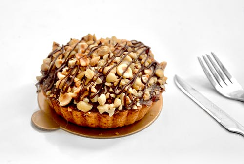 Appetizing sweet pie tart with shortcrust pastry and chopped nuts topped with chocolate sauce on white background near fork and knife
