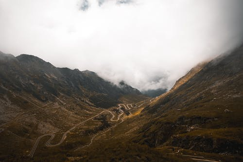 A Picturesque View of a Winding Road in Between Mountains