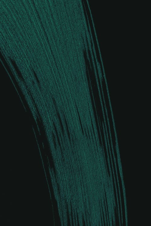 Abstract wide creative smear of paint with green pigment on black clean surface